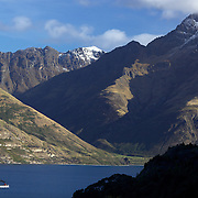 The TSS Earnslaw,  a 1912 Edwardian vintage twin screw steamer on the waters of Lake Wakatipu in, Queenstown, New Zealand. .It is one of the oldest tourist attractions in Central Otago, and the only remaining passenger-carrying coal-fired steamship in the southern hemisphere..The TSS Earnslaw heads along Lake Wakatipu from Queenstown  daily, running tourist trips to Walter Peak Station passing magnificent  peaks and contrasting shoreline foliage along the lakeside. Queenstown, New Zealand. 18th April 2011. Photo Tim Clayton