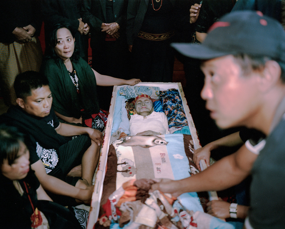 In Torajan culture, death is not necessarily the end.  The body of Lai' Tiku who passed on a few months ago is seen inside the coffin and surrounded by close family members.  Many of her personal belongings are placed inside to accompany her in the after life.  The matriarch in her family, Nenek Lai' Tiku passed away at age 102, she is survived by 10 children, 49 grandchildren, and 162 great-grandchildren.