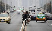 XI'AN, CHINA - OCTOBER 16: (CHINA OUT) <br /> <br /> Crossing Main road is a danger every day<br /> <br /> People stride across  strides across guard bar to cross the road on October 16, 2014 in Xi'an, Shaanxi province of China. 109 passengers used the guard bar to cross the road within 2 hours since there is no pedestrian crossing between a community and a bus station in Xi'an<br /> ©Exclusivepix