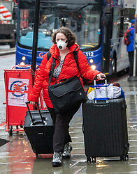 © Licensed to London News Pictures. 28/02/2020. London, UK. A Passengers leaves Victoria Station, London wearing a protective mask as fears of a pandemic increase after six cases of Coronavirus are confirmed in the UK in the last 24 hours. Photo credit: Alex Lentati/LNP