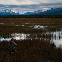 A waterfowl hunter looks for birds as the sun begins to rise.