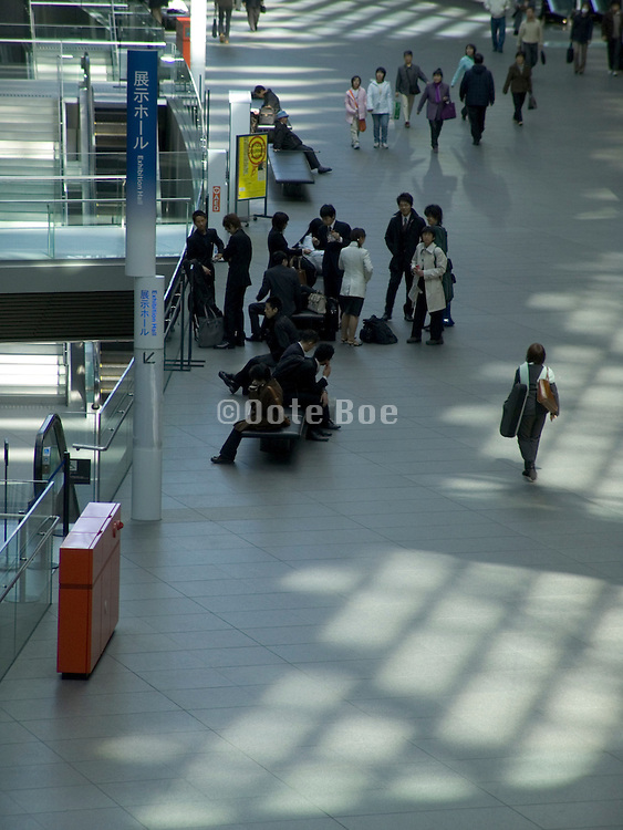people walking in the lobby of large conference hall