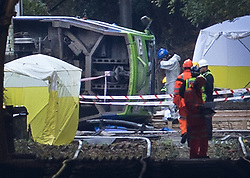 © Licensed to London News Pictures. 10/11/2016. Croydon, UK. A police investigator (in white) prepares to enter the overturned tram near Sandilands station. Investigations are continuing into a tram crash that police say claimed seven lives and injured 50. The driver has been arrested and is being questioned by police. Photo credit: Peter Macdiarmid/LNP