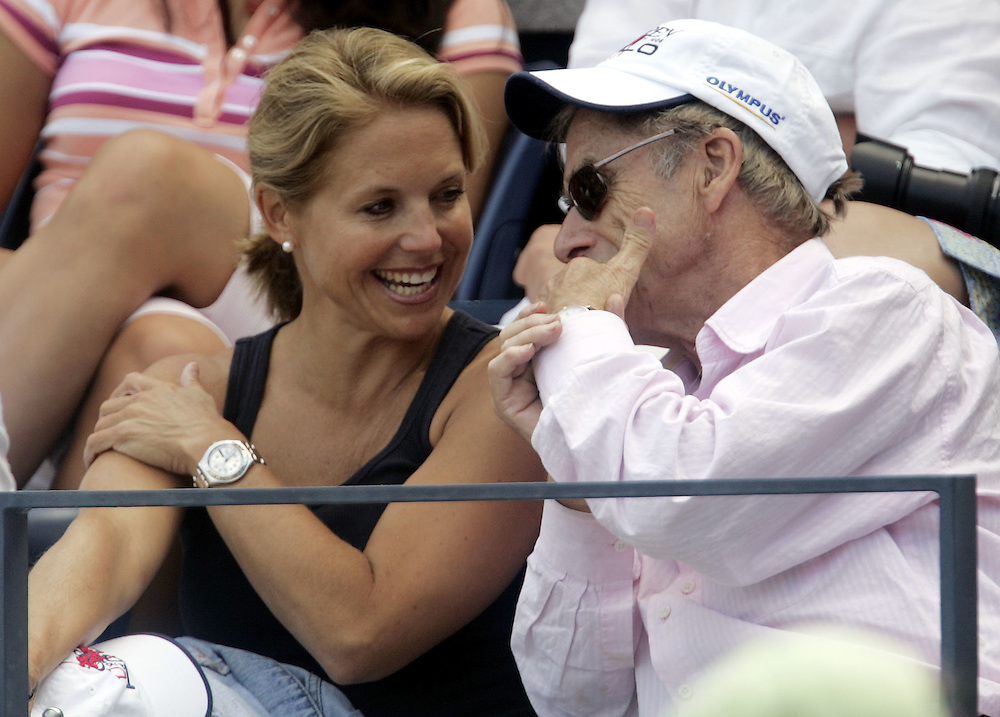 Katie Couric, who starts her new job as the anchor on CBS Evening News on Tuesday 05 September, talks with editor and publisher Harry Evans as she watches the match between Andy Roddick and Fernando Verdasco on the seventh day of the 2006 US Open tennis tournament in Flushing Meadows, New York Sunday, 03 September 2006. The woman at right is unidentified.