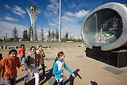 The Baiterek is the New Astana's main symbol and landmark. School girls passing a display of modern Astana.