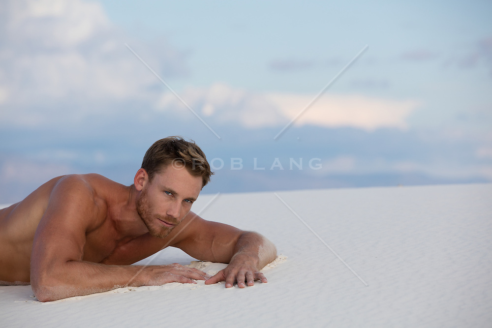 good looking man on a sand dune in New Mexico