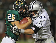 Kennedy's Miles Moa (25) is hit behind the line of scrimmage by Xavier's Andrew Khairallah (71) and loses 3 yards during their game at Kingston Stadium in Cedar Rapids on Friday, September 27, 2013.