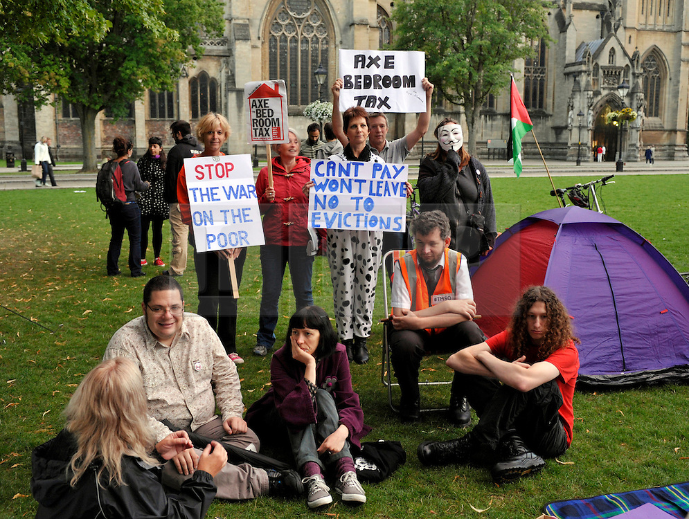 © Licensed to London News Pictures. 24/08/2013. Bristol, UK. Campaigners against the 'Bedroom Tax' hold a sleep over protest on Bristol's College Green in front of Bristol City Hall.  Bristol City Council has said it will not evict tenants who fall into rent arrears due to having their housing benefit cut because they are deemed to have one or more spare bedrooms.  The protesters were given permission to camp overnight on College Green, which is owned by Bristol Cathedral.  18 August 2013.<br /> Photo credit : Simon Chapman/LNP