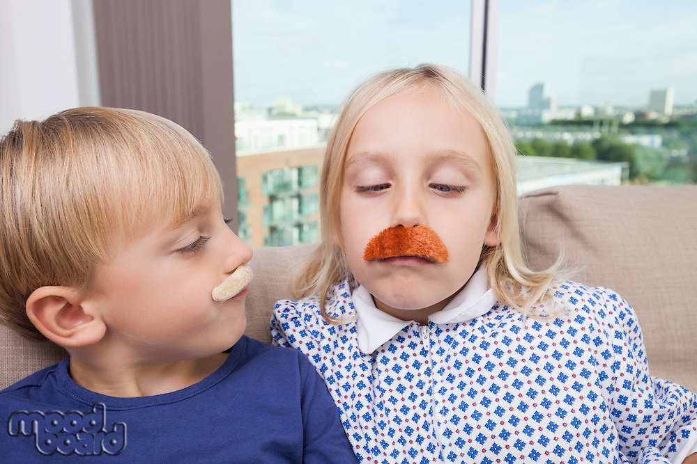 Brother and sister wearing artificial mustache at home