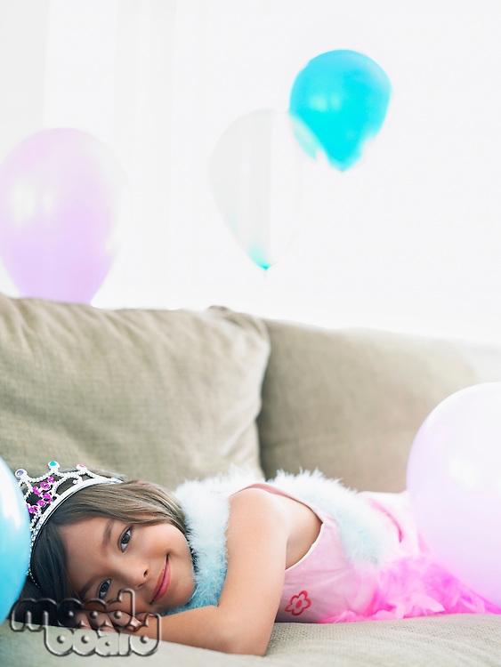 Young girl (7-9) lying on sofa with balloons