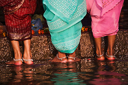 A close up of three pairs of women's feet beneath colorful saris as they stand in the Ganges River on a step of the main Dasaswamedh Ghat in Varanasi, Varanasi, Uttar Pradesh, India