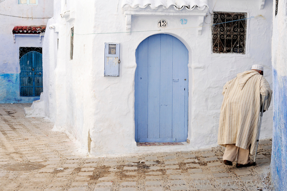 Morocco, Chefchaouen. Man wearing a light jellaba passing the corner of the Chefchaouen blue street.