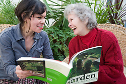 IndependentAge volunteer and older woman looking at a gardening book together,
