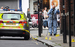 © Licensed to London News Pictures. 29/05/2016. London, UK.  A member of a police forensics team takes photographs at  the scene where a man in his 30's was stabbed in the early hours of the morning in Camden High Street. Police were called at 03:46hrs on Sunday, 29 May to Camden High Street close to Greenland Road following reports of a man suffering a stab wound. Officers and the London Ambulance Service attended. The man, believed to be aged in his late 30s, was taken to a central London hospital where he died at 04:37hrs. Photo credit: Ben Cawthra/LNP