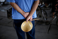 A worker waits for a free meal at a communal dining hall in the model village of Nan Jie Cun, China, Wednesday, Aug. 26, 2009.  Nan Jie Cun village in central China's Henan province advertises itself as a commune which continues to adhere to the communist teachings of Mao Zedong, who founded the People's Republic 60 years ago. The village's industries are collectively owned. Workers receive bonds, instead of currency, and housing and healthcare are free. They sing revolutionary songs and march to work in lines. Despite being out of step with the rest of today's China, the village's industries are a success, and more than 7,000 migrants have requested to work at Nan Jie Cun.