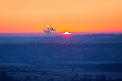 © Licensed to London News Pictures. 12/12/2017. North Rigton UK. The sun rises behind Ferry Bridge power station this morning seen from the top of Almscliffe Crag, a Millstone Grit outcrop in the village of North Rigton near Harrogate. Photo credit: Andrew McCaren/LNP