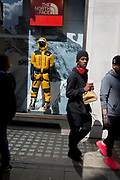 Youths walk past the fully kitted-out mannequin of a mountaineer in the window of outdoor equipment retailer The North Face on Regent Street, on 18th April 2017, in London, England.