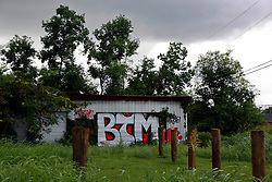 23 August 2013. Lower 9th Ward, New Orleans, Louisiana.<br /> Katrina 8 years later. Graffiti on a run down building. In a tale of two cities, the hardest hit neighbourhoods struggle to revitalize and return. Many half finished or blighted properties and vacant overgrown lots remain dotted throughout the landscape with limited new construction projects. Residents who have returned complain of limited services, infrequent police patrols, high crime rates, rampant mosquitos and uncontrolled vermin. <br /> Photo; Charlie Varley