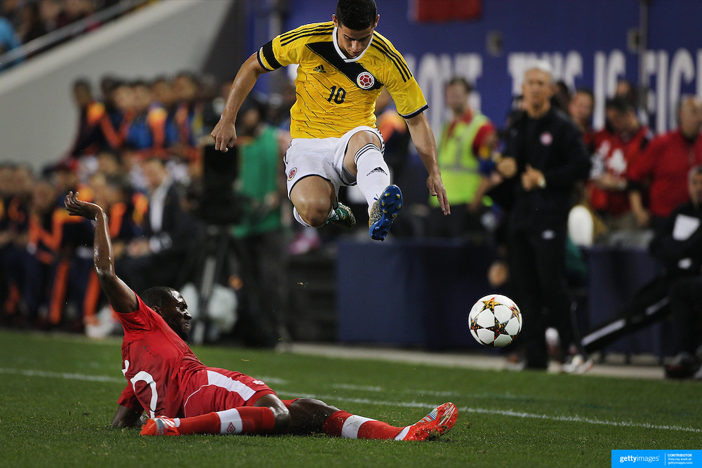 James Rodríguez, Colombia, jumps to avoid the challenge of Doneil Henry, Canada, during the Columbia Vs Canada friendly international football match at Red Bull Arena, Harrison, New Jersey. USA. 14th October 2014. Photo Tim Clayton