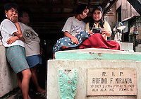 Jeanelyn Roda, 14, right, passes a late afternoon listening to a radio with friend Maricel Bacale, 15, from on top a tombstone in the Cavite City Cemetery.(Janet Jensen/The News Tribune)