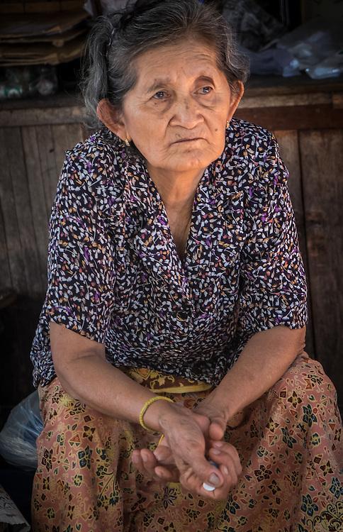 MAE KLONG - TAHILAND - CIRCA SEPTEMBER 2014: Woman seating in the streets of the Maeklong Railway Market