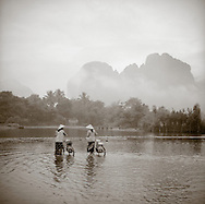Two women wearing traditional conical asian hats with bicycles cross the river in Vang Vien, Laos. In the distance are the limestone mountains looming in the mist.