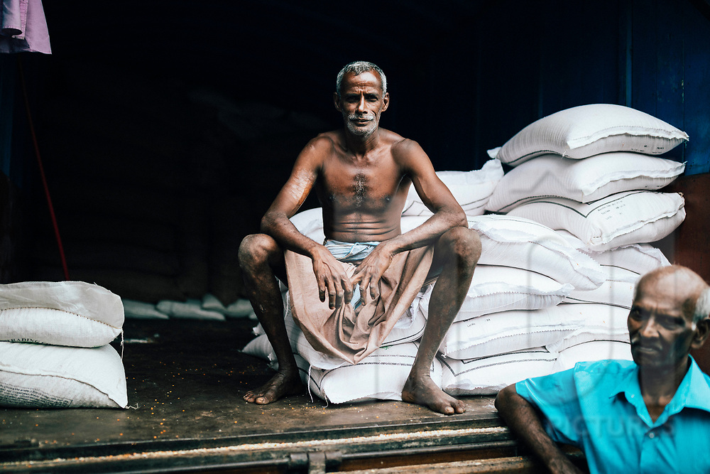 A worker at a local fresh market, taking a break from unloading bags of grain, Kandy, Sri Lanka, Asia