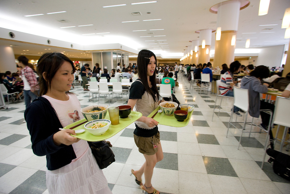 Tokyo's Toyo University's  New  Food court one of the many  improvments being developed to help  Japan's Universities compete for an ever decreasing levels of student enrollment  due to declining population.  A  decline in the Japanese birthrate has cause school closings nationwide which is reflected in Primary and High School consolidations and closings and recently is effecting Universities as well...Eri  Imai 21 right )  and Maya Amano 21 are visiting  the  Toyo University  food Court