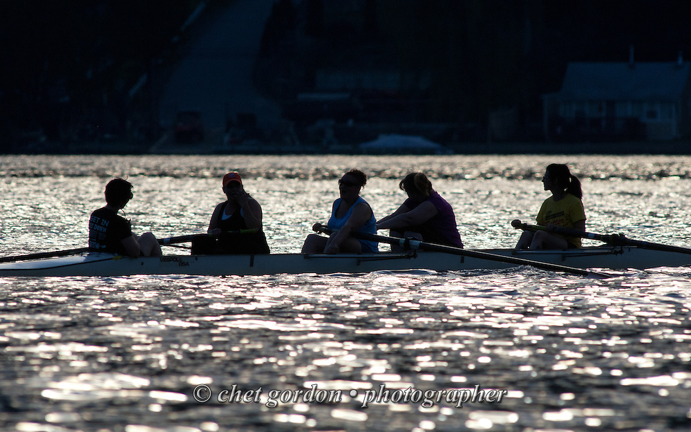 A women's team of four rowers and thier coxswain pause during an evening row on the East Arm of Greenwood Lake in Greenwood Lake, NY on Tuesday, May 26, 2015.  © Chet Gordon/THE IMAGE WORKS