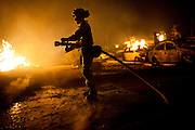 SAN BRUNO, CA - SEPTEMBER 9: Cal Fire firefighter Martin Medina mops-up a fire September 9, 2010 in a San Bruno, California residential street. A massive explosion rocked a neighborhood near San Francisco International Airport.