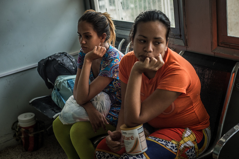 PUERTO LA CRUZ, VENEZUELA - APRIL 16, 2016: Lisquer Pulido, 17, (left) and Marilin Mago, 25, (right) wait to enter the neonatal area of the maternity ward to feed their premature babies that had been born that week. All mothers must either breast feed or bring their own formula, because the hospital does not have any.  Ms. Mago clutches a can of baby formula, she said she can't breast feed because she doesn't have enough to eat herself, so can't produce breast milk. Hospital Universitario Dr. Luís Razetti is one of the worst state-run, public hospitals in Venezuela.  Doctors compare it to working in a war zone - they regularly have to turn patients away, because they don't have the majority of medicines  or medical equipment and supplies needed to give them medical attention.  When they do accept patients, they have to work with extremely limited resources, because they don't have the supplies they need for things like X-Rays,  and many exams nd operations.  The hospital's infrastructure is crumbling, and staff don't have all the cleaning supplies required to keep the hospital sanitary. The hospital also suffers from weekly shortages of running water and electricity.  In April, several babies died when a power outage turned off the incubators, and the hospital's generator failed to work because of lack of maintenance.  The same month, authorities found over 100 pieces of medical equipment, stolen from the hospital in the home of the assistant to the hospital's director.  Despite having the largest oil reserves in the world, falling oil prices and wide-spread government corruption have pushed Venezuela into an economic crisis, with the highest inflation in the world and chronic shortages of food and medical supplies.  PHOTO: Meridith Kohut