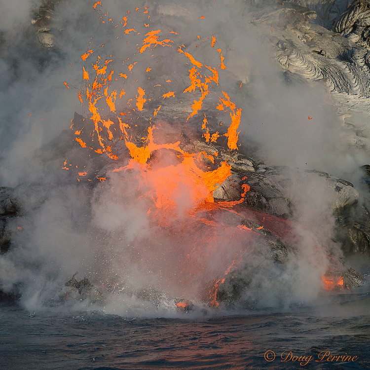 hot lava from Kilauea Volcano erupting from coastal lava tubes, spatters into the air as it enters the ocean offshore from Hawaii Volcanoes National Park, Puna, Hawaii ( the Big Island ), Hawaiian Islands, U.S.A. ( Central Pacific Ocean )