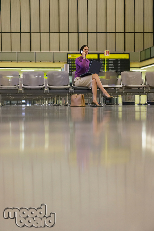 Business woman using mobile phone in airport lobby
