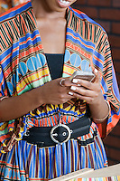 Midsection of woman in traditional African print attire using cell phone