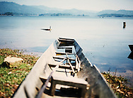 Small broken row boat on the shore of Nam Ngum Lake, Vientiane Province, Laos, Southeast Asia