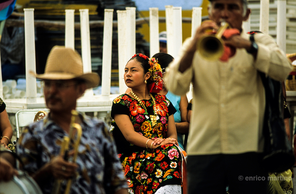 """Juchitàn, Velas (traditional celebrations) of Ixtepec.  """"Regada de Frutas"""", a procession along village's streets. The tehuanas are the archetype of an ancient and legendary Mexico, told in the murales of Diego Rivera and impersonated also by Frida Kalho that often wore these traditional dresses. But these showy dresses, and the rich golden ornaments that accompany them, are above all an instrument of auto-representatiom for these active women who often control the local economy and markets with an independent economic power reflected in their self confidence. Even in the festivities, where the women often dance a lot among them while the men remain seated watching."""