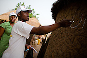 A health worker and a community volunteer mark a home with chalk to indicate that children have been vaccinated during a national polio immunization exercise in the village of Kpalbe, northern Ghana on Thursday March 26, 2009.