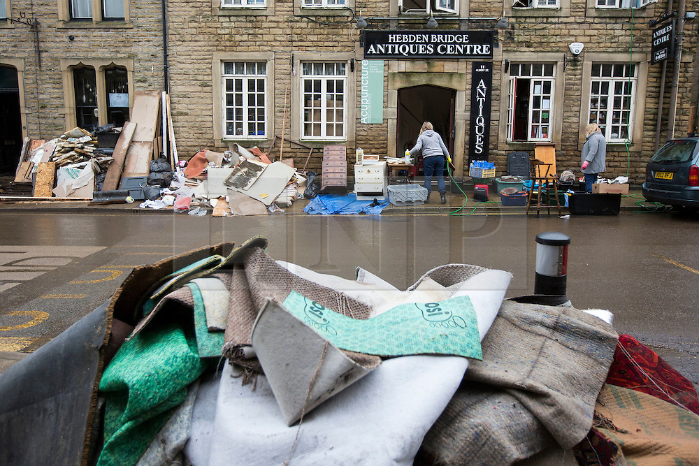 © Licensed to London News Pictures. 28/12/2015. Hebden Bridge UK. A huge clean up operation has begun in Hebden Bridge after the River Calder broke it's banks & flooded homes & business' in the village centre. Photo credit: Andrew McCaren/LNP