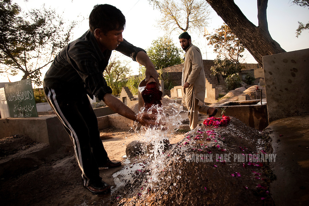 """LAHORE, PAKISTAN - MARCH 24: A worker tends to the grave of Faheem Shamshad who was shot down by CIA contractor, Raymond Davis, as his cousin Ijaz Amhmet (R) watches, on 24 March, 2011, in Lahore, Pakistan. Davis, CIA contractor and former US soldier, shot and killed 2 Pakistan men on January 27, he claimed were armed and attempting to car-jack him in a busy intersection of Lahore. In spite of his diplomatic immunity, Davis was arrested, imprisoned and charged with murder before he was released on March 16, when the US government paid """"blood-money"""" to the victims' families. The incident sparked a major diplomatic furore, widespread protests and the deterioration of US-Pak ties, which would only further weaken in the coming months when Osama bin Laden was killed by US Navy Seals hiding in the Pakistani military garrison town, Abbottabad.  (Photo by Warrick Page)"""