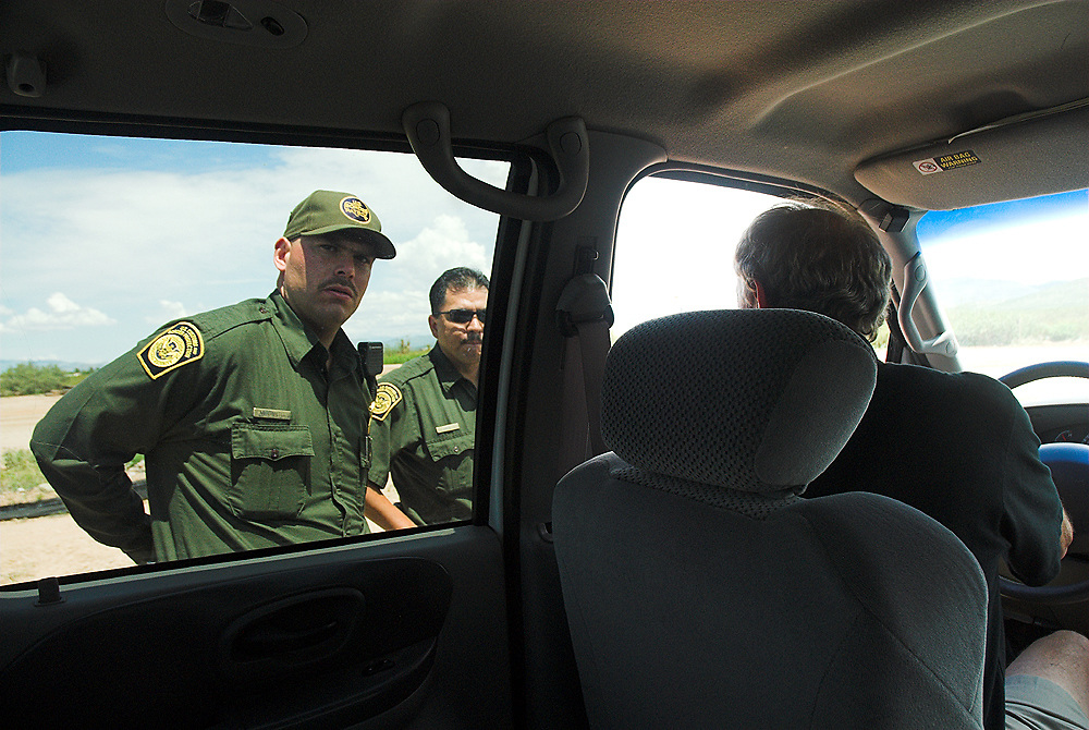 Ray Borane, mayor of Douglas, Arizona, is stopped and questioned by Border Patrol agents as he drives along the border fence. On the other side of the border sits the town of Agua Prieta, Mexico. Many Mexicans have cut through the fence in order to get across the border and find a new life in the U.S.