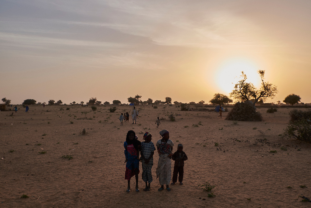 Children stand in a camp of internally displaced people by the side of the road on the highway outside of Diffa, Niger on February 11, 2016.Caritas undertook a distribution of two blankets per family in January, 2016. Most of the displaced families are from the village of Chilori, Niger close to the border with Nigeria and fled when Boko Haram attacked killing 10 people.