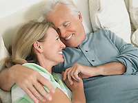 Couple embracing lying in bed elevated view