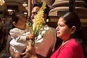 04 APRIL 2004 - SAN MIGUEL DE ALLENDE, GUANAJUATO, MEXICO: A family at Palm Sunday service in Iglesia San Francisco, a Catholic church in San Miguel de Allende, Mexico, April 4. Palm Sunday is the reenactment of Christ's entry in Jerusalem and marks the first day of Holy Week. Holy Week is celebrated throughout central Mexico with Processions and special masses. PHOTO BY JACK KURTZ