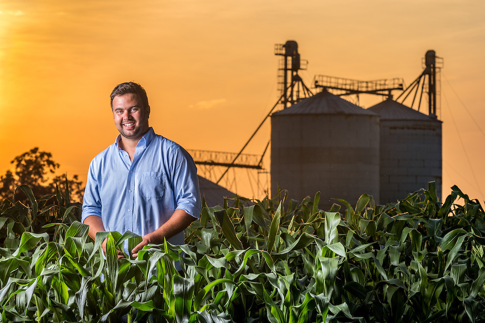 A local Maryland farmer posing in a corn field while the sun sets over the farm.
