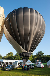© Licensed to London News Pictures. 08/08/2015. Bristol, UK. Day 3 of the Bristol International Balloon Fiesta 2015.  The world's first solar powered hot air balloon which made its debut at the Bristol International Balloon Fiesta.  The black side of the balloon heats up the air inside and the white side reflects the heat back in.  By turning the ballon the pilot can control the heat of the air inside to raise and lower the balloon, which also has standard gas burners for safety and to aid lift off.  Photo credit : Simon Chapman/LNP