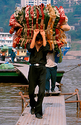 CHINA SICHUAN PROVINCE CHONGQUING MAY99 - A Chongquing dockworker carries carpets from a ferry at Chiaotianmen docks in Chongquing. Seven large cities, including Chongquing, and thousands of villages will be submerged once the water level rises after the completion of the controversial Three Gorges Dam project further downriver. The flooding of areas reaching back more than 550Km upriver will require the evacuation and resettlement of more than 10 million people.  jre/Photo by Jiri Rezac. © Jiri Rezac 1999. . Contact: +44 (0) 7050 110 417. Mobile:  +44 (0) 7801 337 683. Office:  +44 (0) 20 8968 9635. . Email:   jiri@jirirezac.com. Web:     www.jirirezac.com