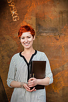 Young attractive businesswoman standing while holding document