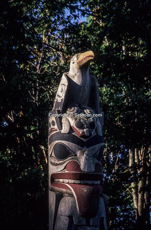 Canada. Vancouver . anthropology museum of BC university . totem poles   - Haidas -  Indian houses carved ; artist Bill Reid  /  totems et maisons des indiens  - Haidas -  par l'artiste Bill Reid, BC université; Vancouver.      /    Oeuvre de Bill Reid. L'Université de Colombie Britannique (UCB) à Vancouver, la collection permanente du Musée d'Anthropologie (MA). Double monument funéraire au blason du Squale, en premier plan; en arrière plan: deux maisons traditionnelles haida. (Hauteur: 25 pieds) (MA-UCB). La maison située à gauche est une maison funéraire.