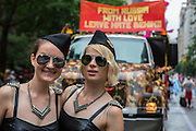 "Two young women in vaguely Russian-looking military caps pose in front of a truck in the parade that bears a sign reading ""From Russia with love leave hate behind."""