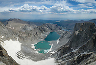 """This was my view while I ate lunch on Cloud Peak, the highest point of the Bighorn Mountains. I timed this 25 mile long, 3 day backpacking trip with the hottest day of the year. While the temperature topped 100°F down in the valley, up here at 13,167 feet it was much more pleasant in the 60's. At this high elevation the boiling point of water is 25° cooler than at sea level. In the cirque 1500 feet below lies the Cloud Peak Glacier. It is the only glacier in the Bighorns and is predicted to be gone 20 years from now. As the compressed snow and ice slowly slides down the mountain slope, it grinds up the bedrock beneath it and forms a very fine silt called """"rock flour"""". This flour becomes suspended in the glacial meltwater and gives the lake it's greenish-turquoise color that changes with the lighting conditions. In the hour I spent on the summit I heard the sound of numerous rockfalls. Some of them would cause a chain-reaction lasting a minute or longer."""